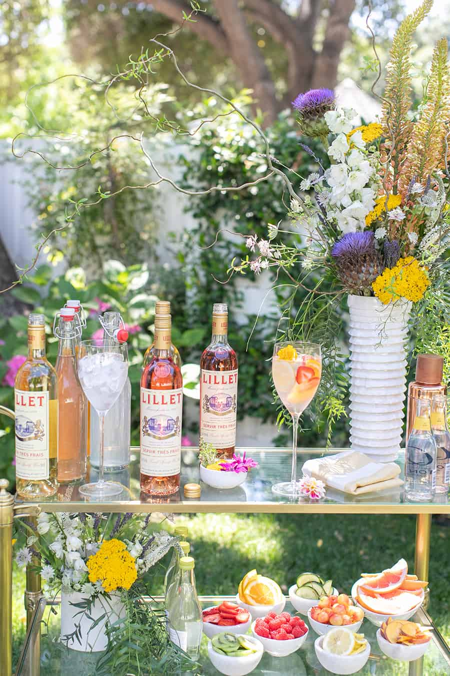 Bottles of Lillet on gold bar cart with flowers.