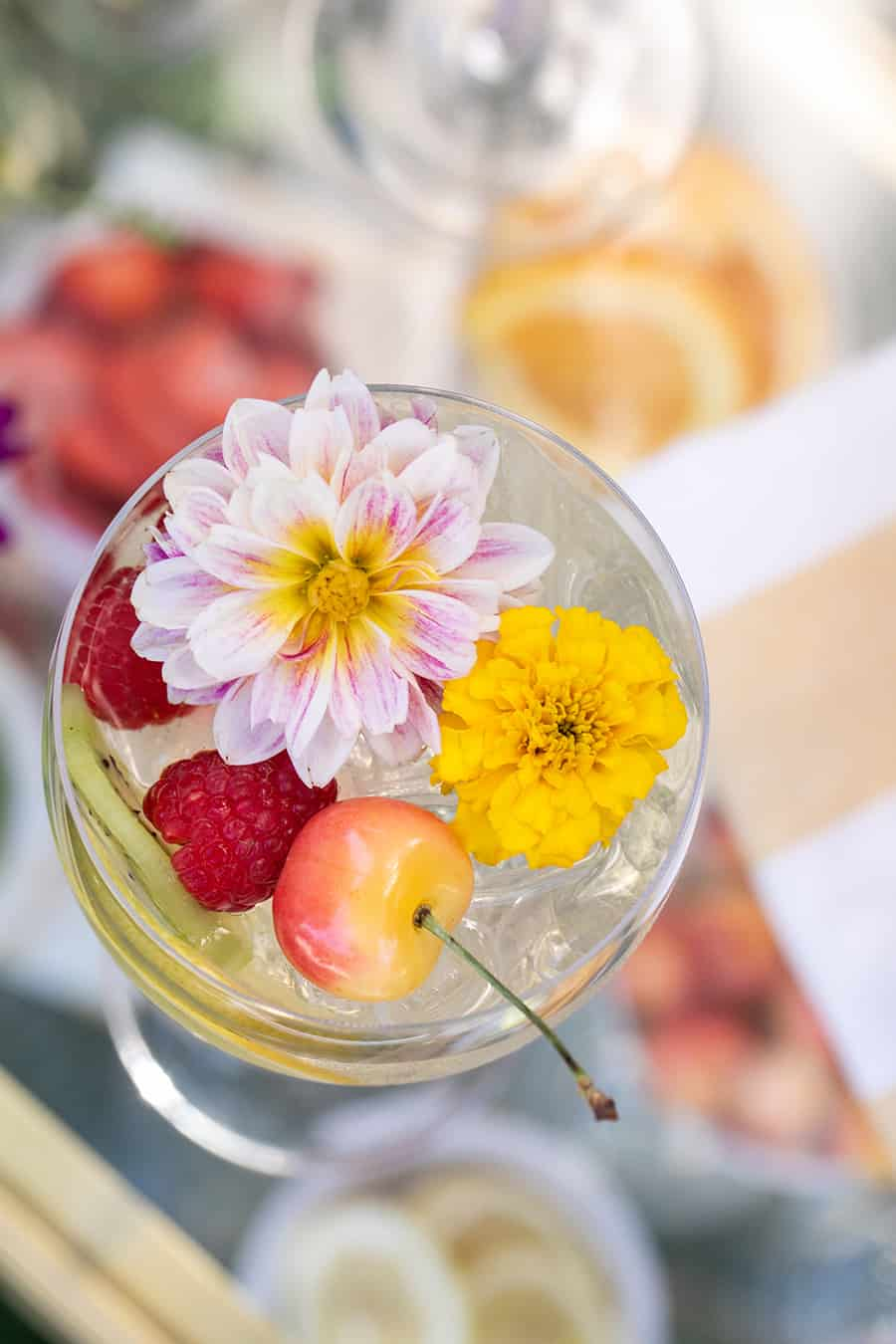Overhead of cocktails with edible flower and cherries.