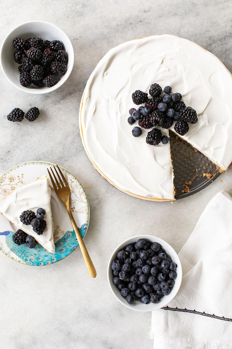 Overhead cheesecake with blueberries and blackberries. A plate of cheesecake and a bowl of berries on a marble table.