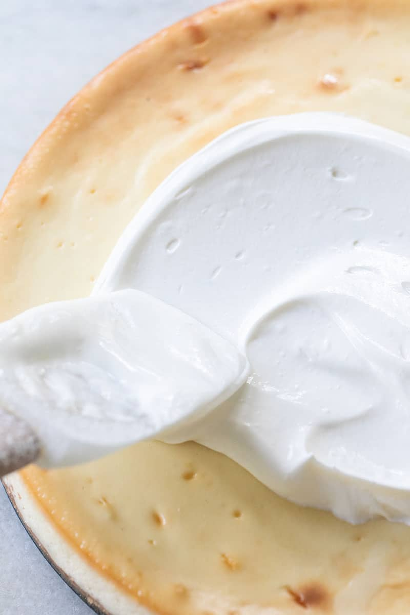 Whipped sour cream spread over cheesecake with spatula.