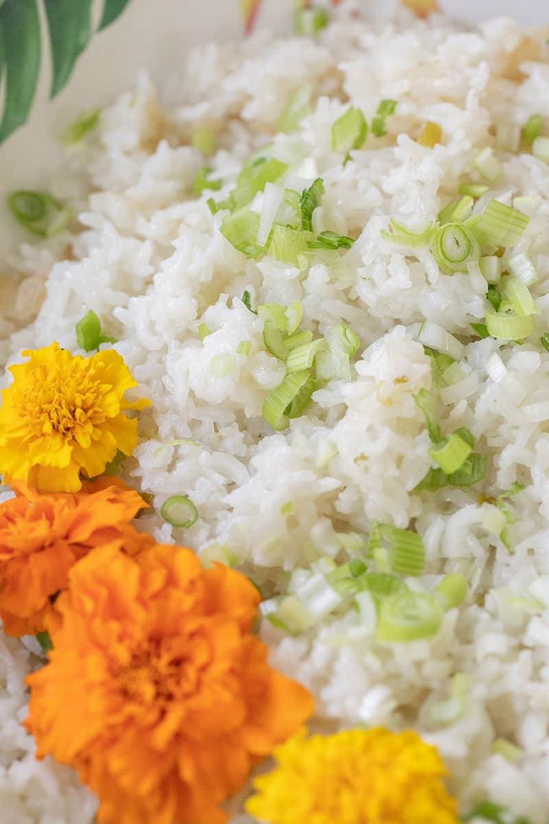 close up of coconut rice with scallions and flowers.