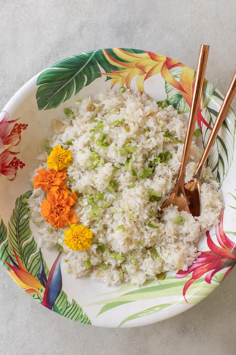 Bowl of coconut rice with copper serving spoons.