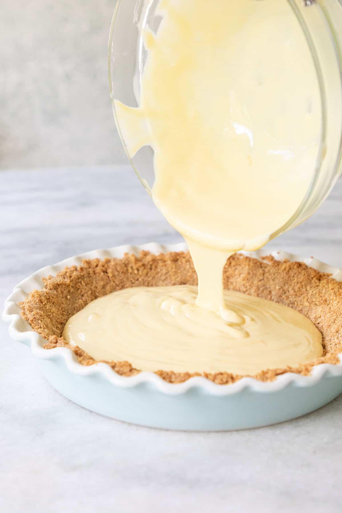 pouring lemonade pie filling into a pie dish
