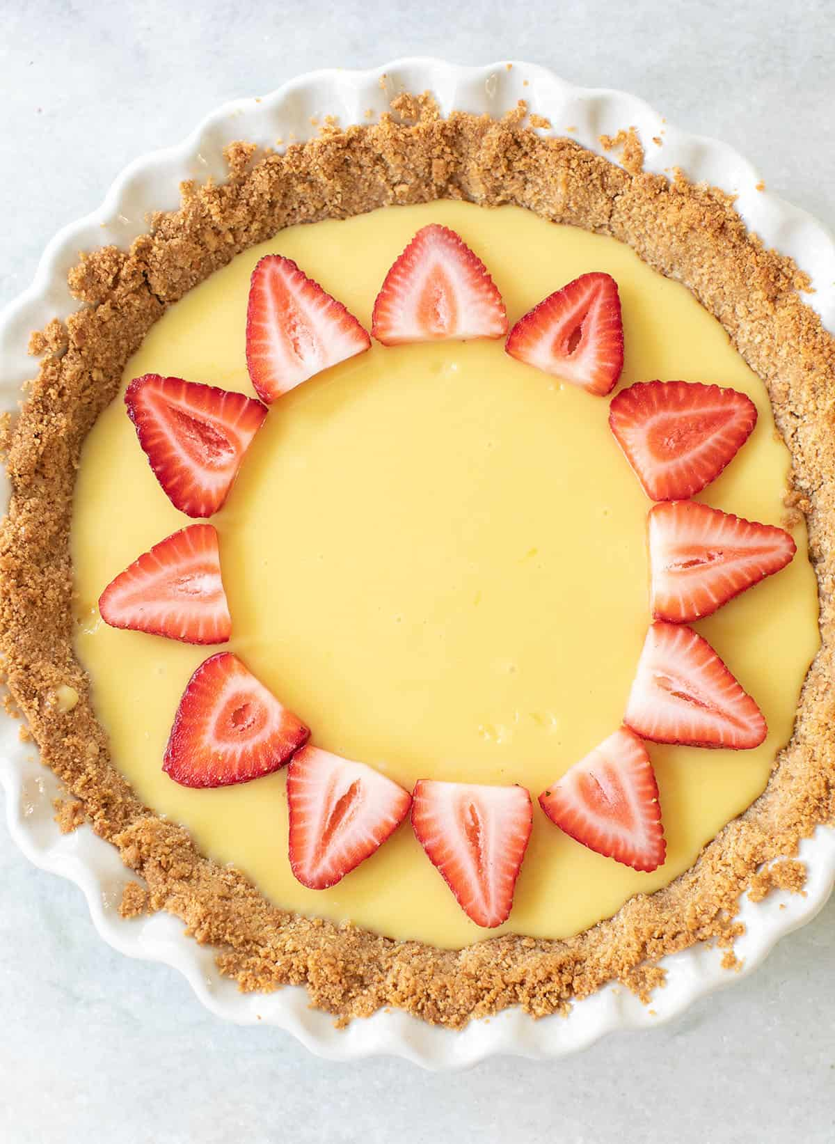 pie recipe made with lemon juice with sliced strawberries over the top