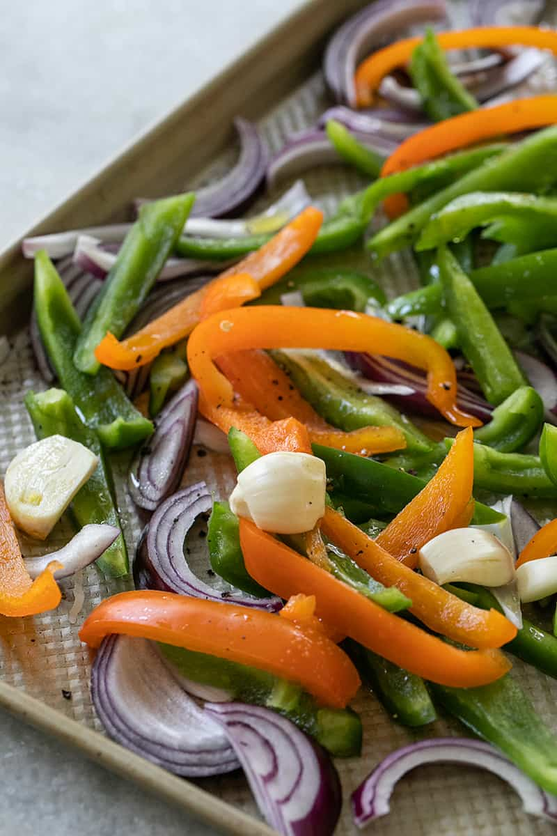Sliced green and orange peppers with onions and garlic on a sheet pan tossed with olive oil