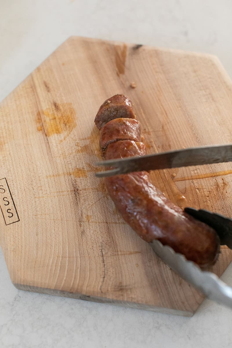Slicing sausage on a wood cutting board.