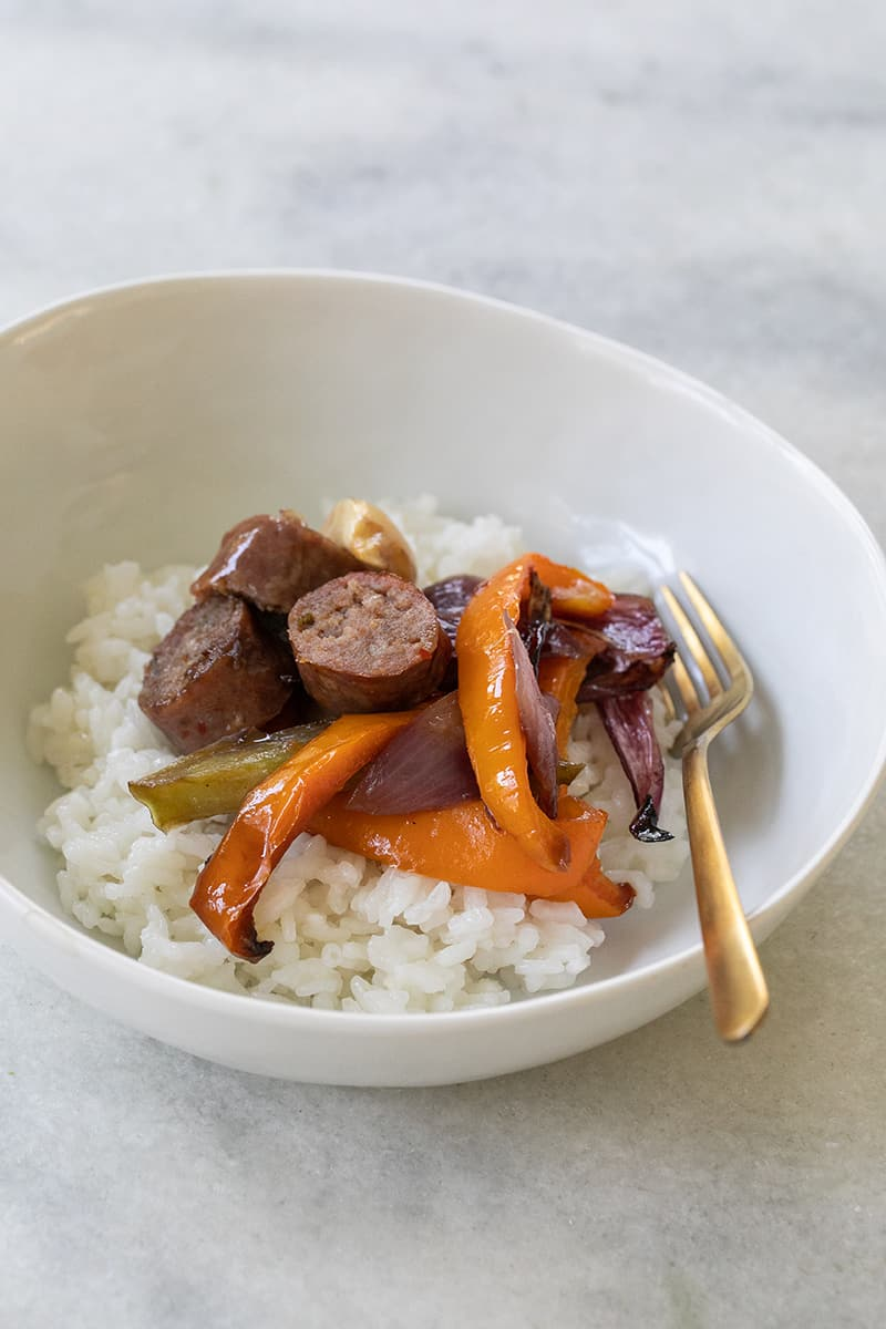 Sausage and Peppers in a bowl with white rice.