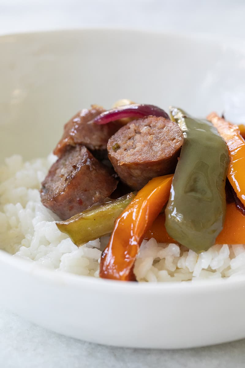 Sausage and peppers on white rice in a white bowl.