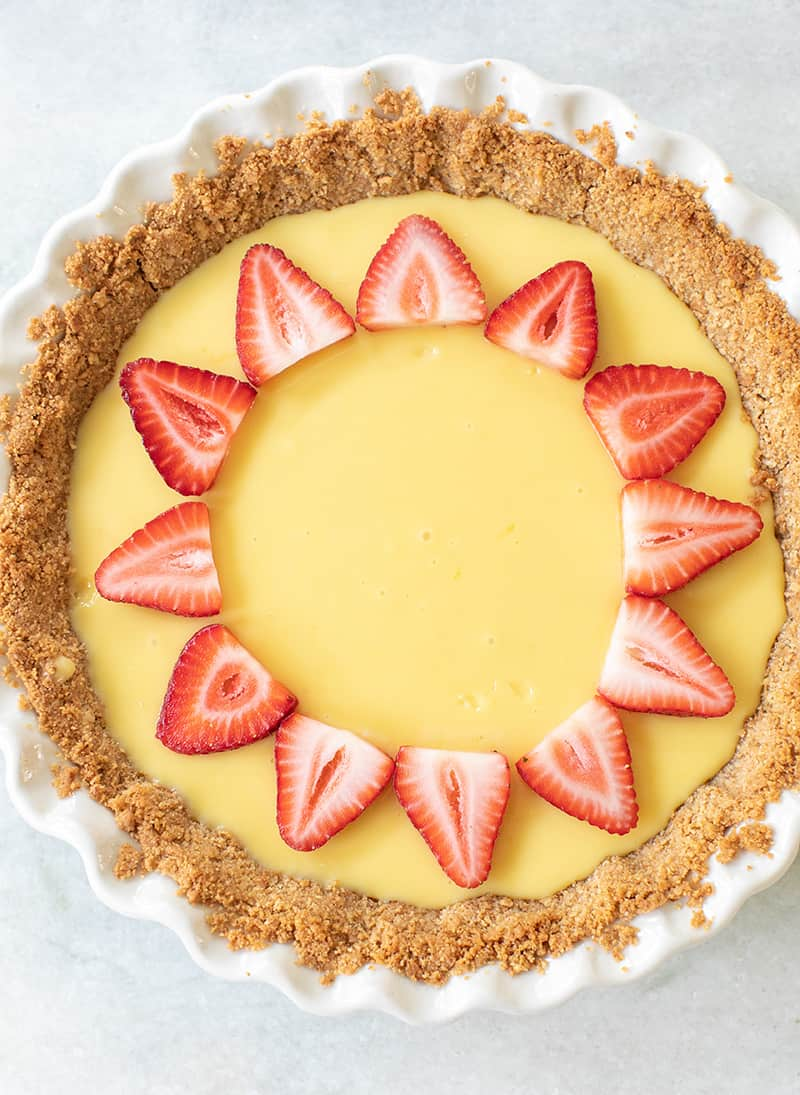 Top view of strawberry lemonade pie with sliced strawberries on a marble table.