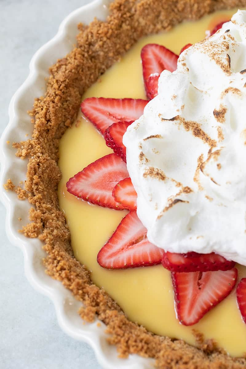 Close up of whipped toasted meringue on top of strawberry lemonade pie.