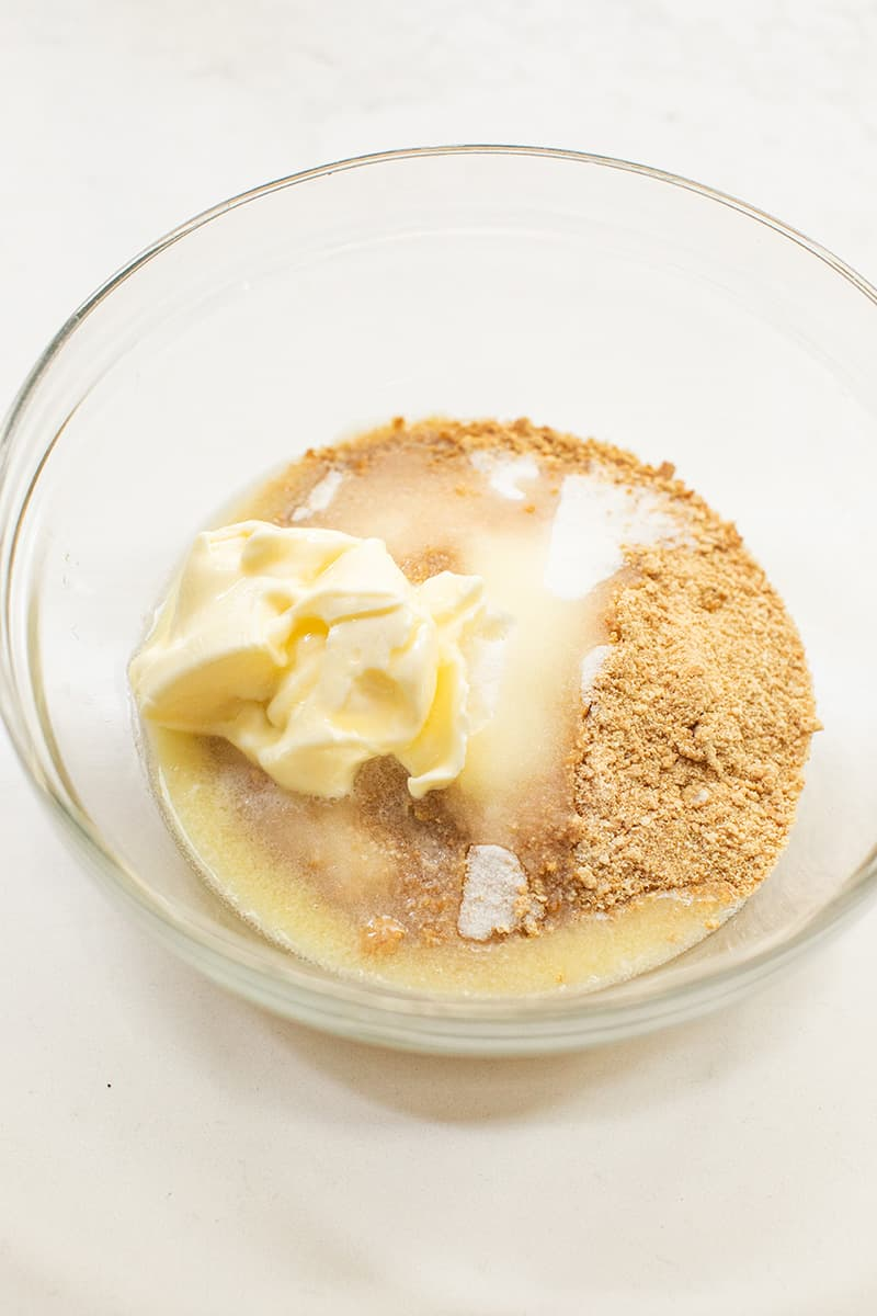 Melted butter in a bowl with graham cracker crumbs.