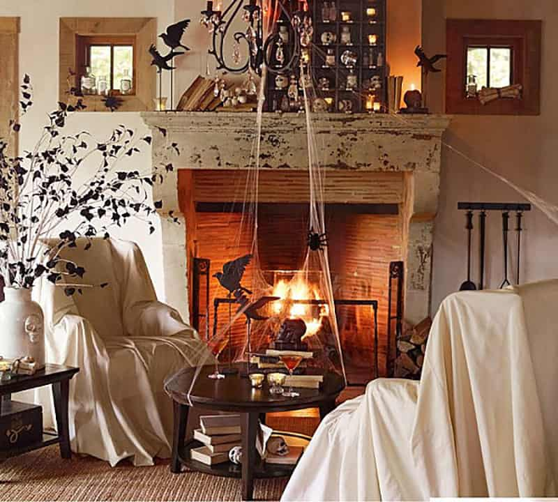 Spooky Halloween living room with sheets over the chairs, birds and bats and a lit fireplace.