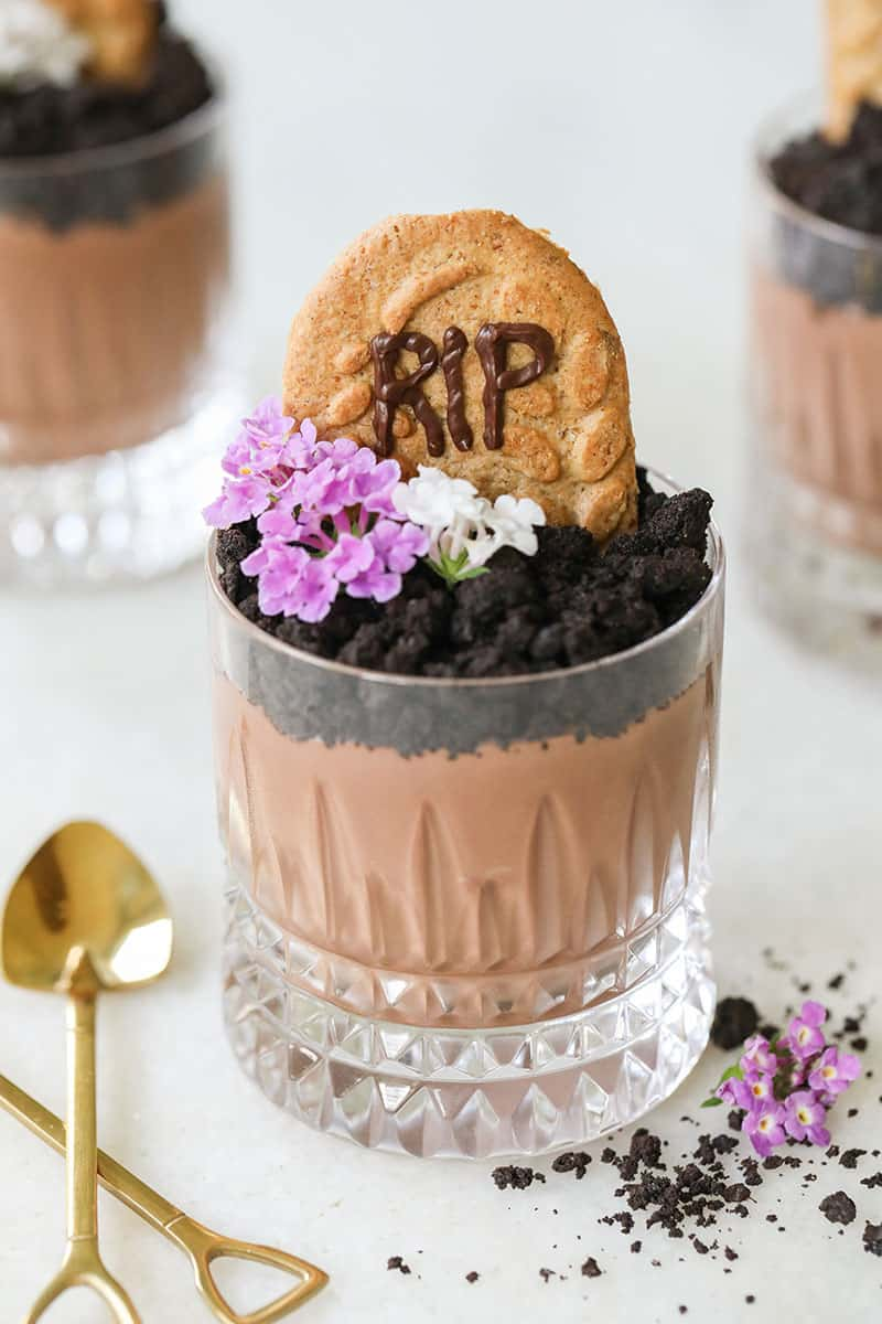 The cutest Halloween Dirt Cups with crushed Oreos, flowers and a cookie tombstone.