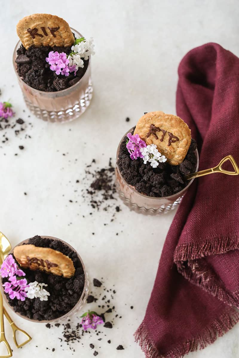 Halloween dirt cups with gold shovel spoons and a plum colored napkin.
