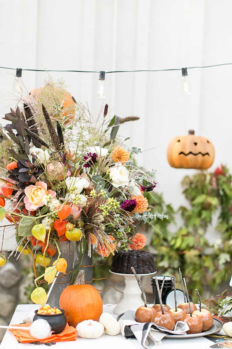 Flowers, pumpkins and candy apples on a white wooden table.