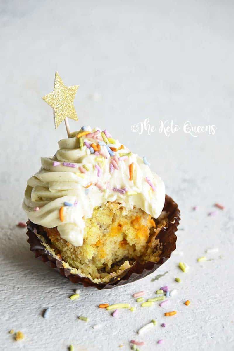 Cute vanilla bean Keto cupcakes with bite taken out and sprinkles on top with a gold star.