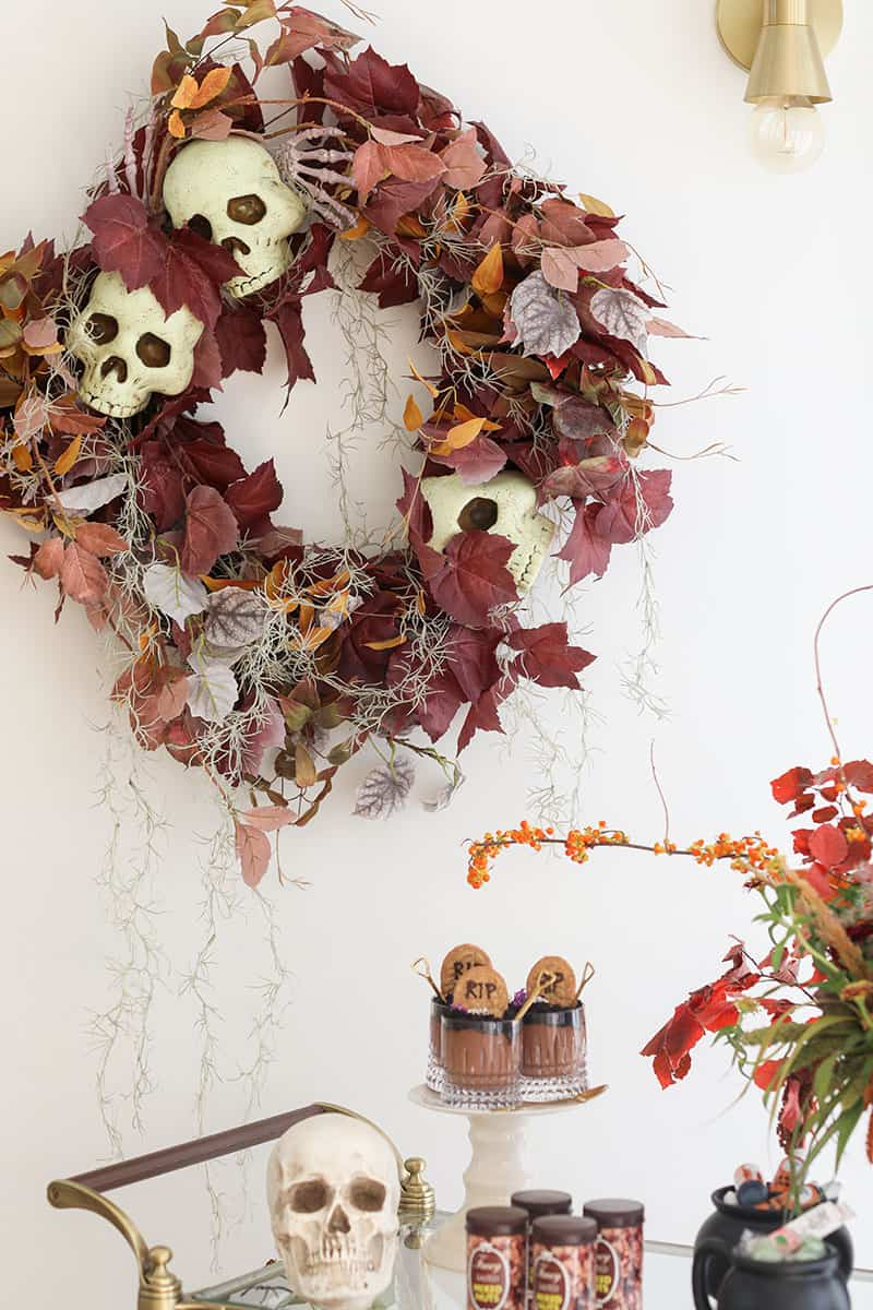 Halloween wreath and decorations on a bar cart for a Halloween party