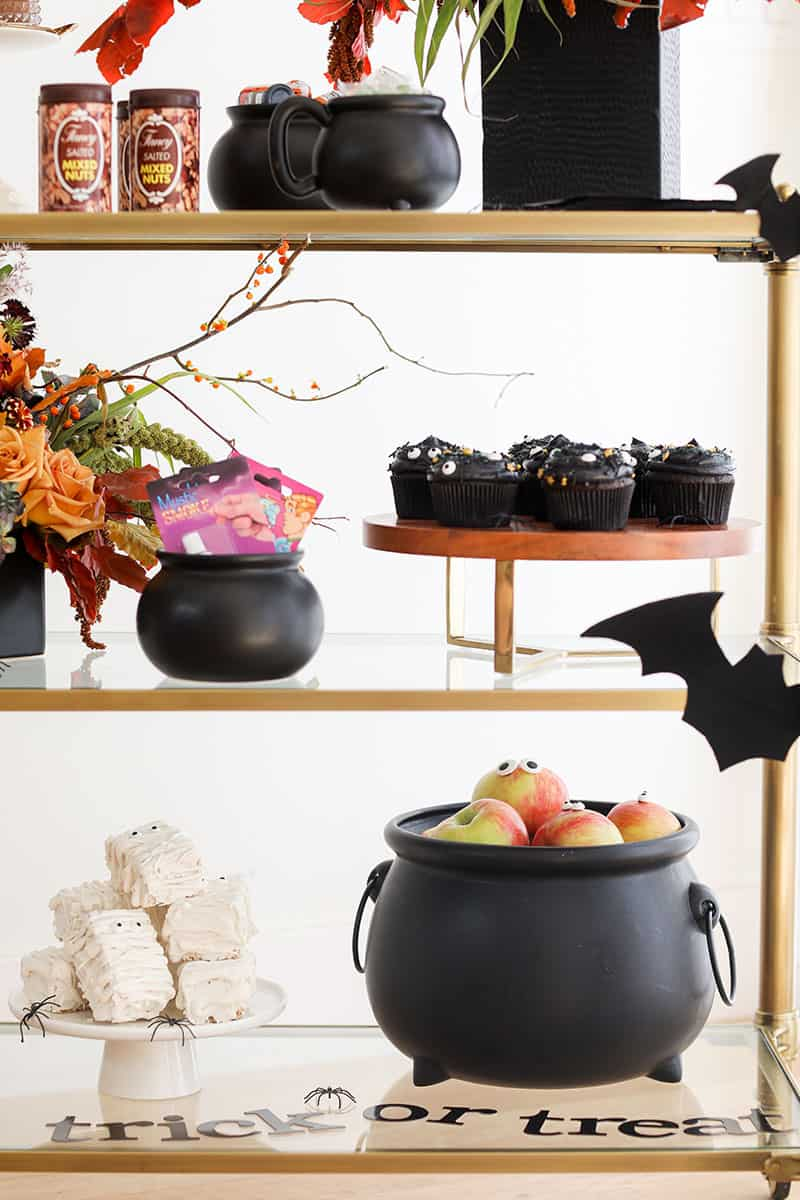 Party decorations, large cauldron with apples, bats, cupcakes and tricks.