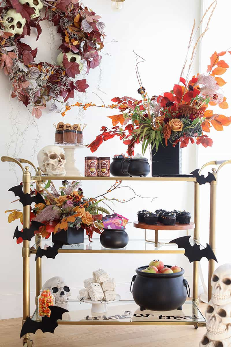 Halloween party bar cart filled with tricks and treats like cupcakes, mummy rice krispies treats, skulls, bats and flowers.