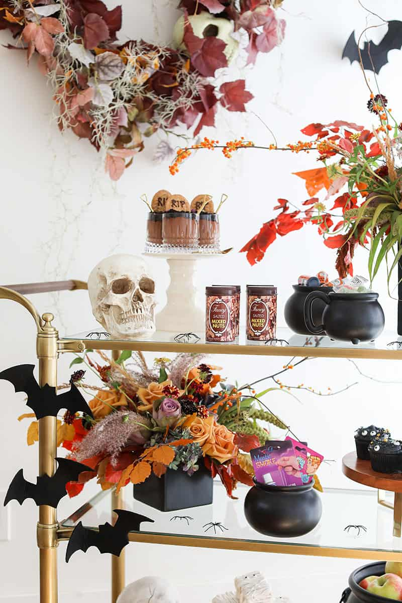 Halloween Party set-up with tricks and treats on a gold bar cart.