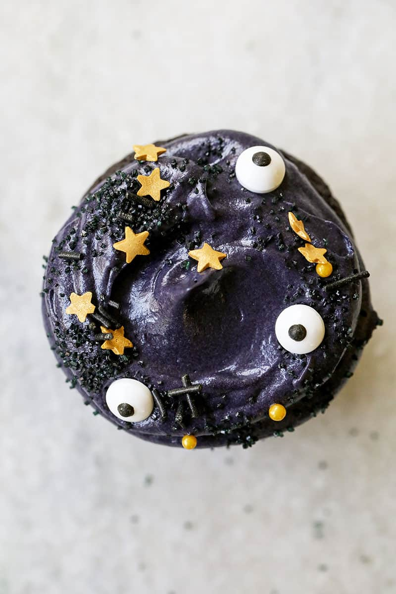 Black velvet cupcake topped with whipped cream cheese frosting and eyeball sprinkles.