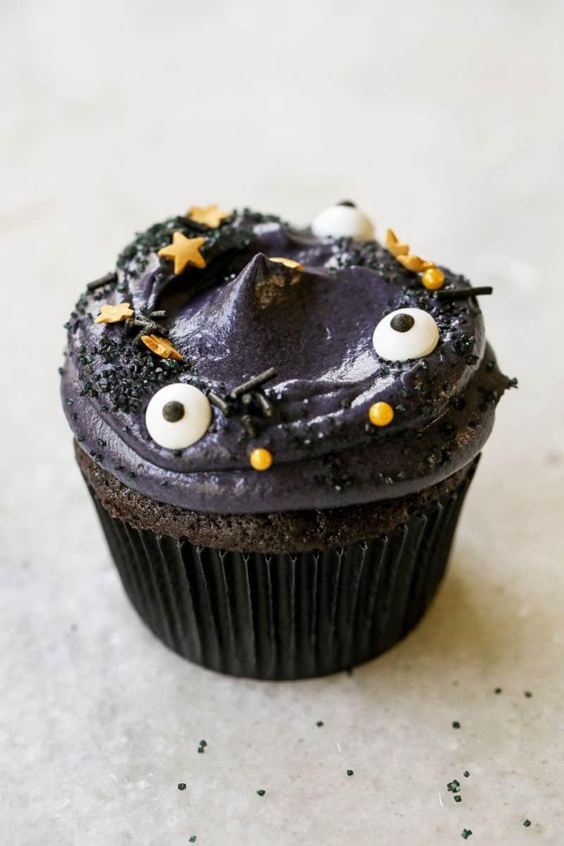 A spooky black velvet cupcake with eyeball sprinkles and gold stars for Halloween.
