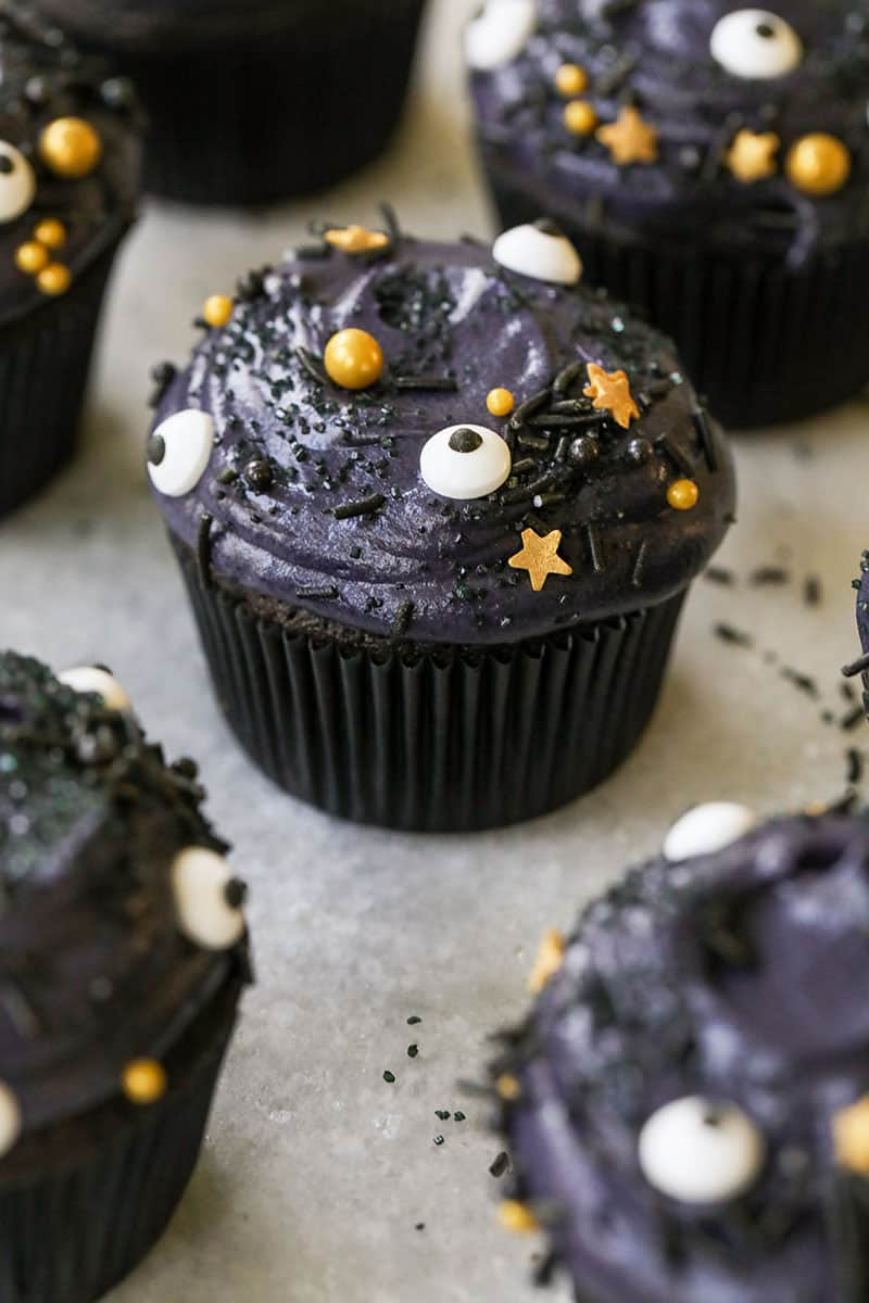 Spooky black velvet cupcakes with eyeball sprinkles and gold starts with a black cupcake liner.