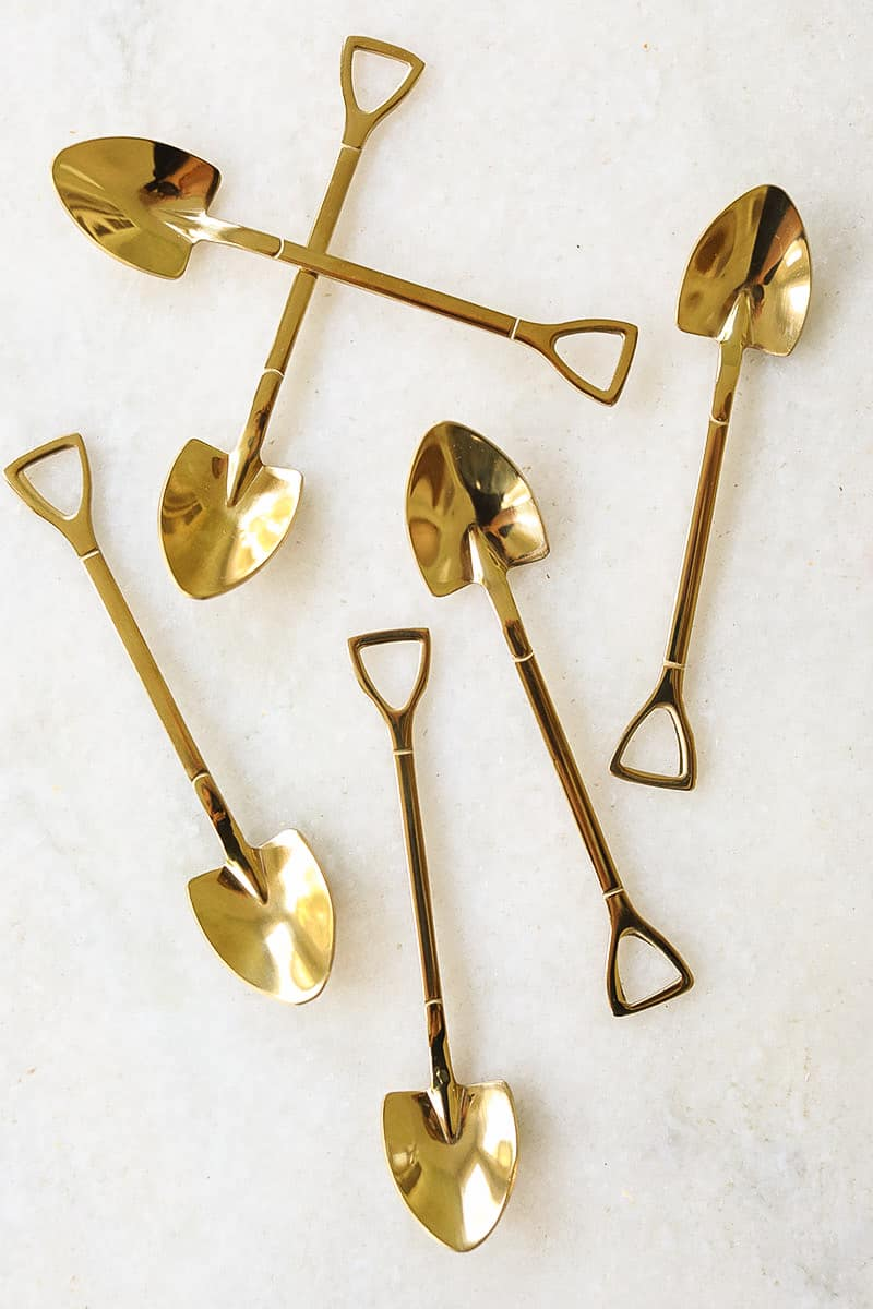 Gold shovel spoons on a marble table.
