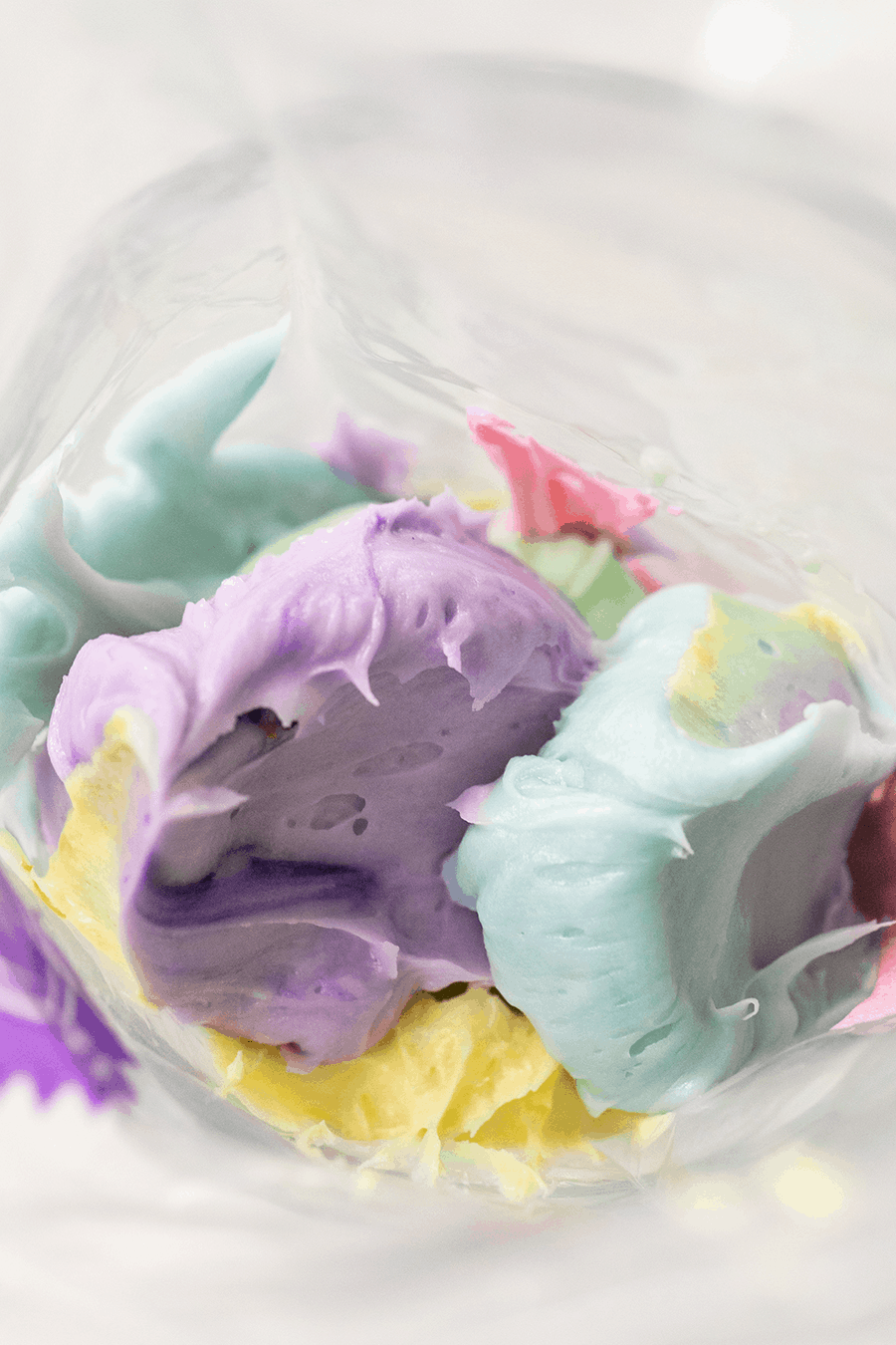 Colorful buttercream frosting in a piping bag.