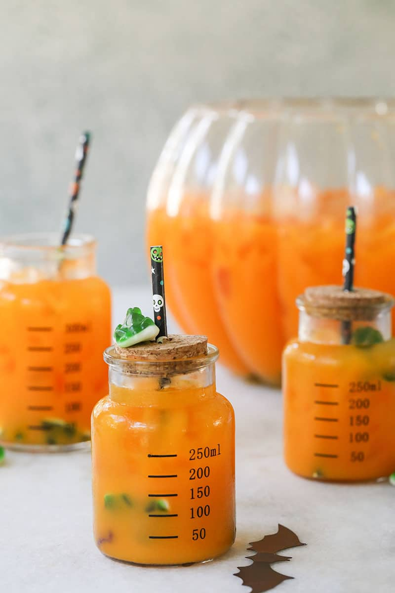 Orange Halloween punch in a beaker with cork and a Halloween straw.