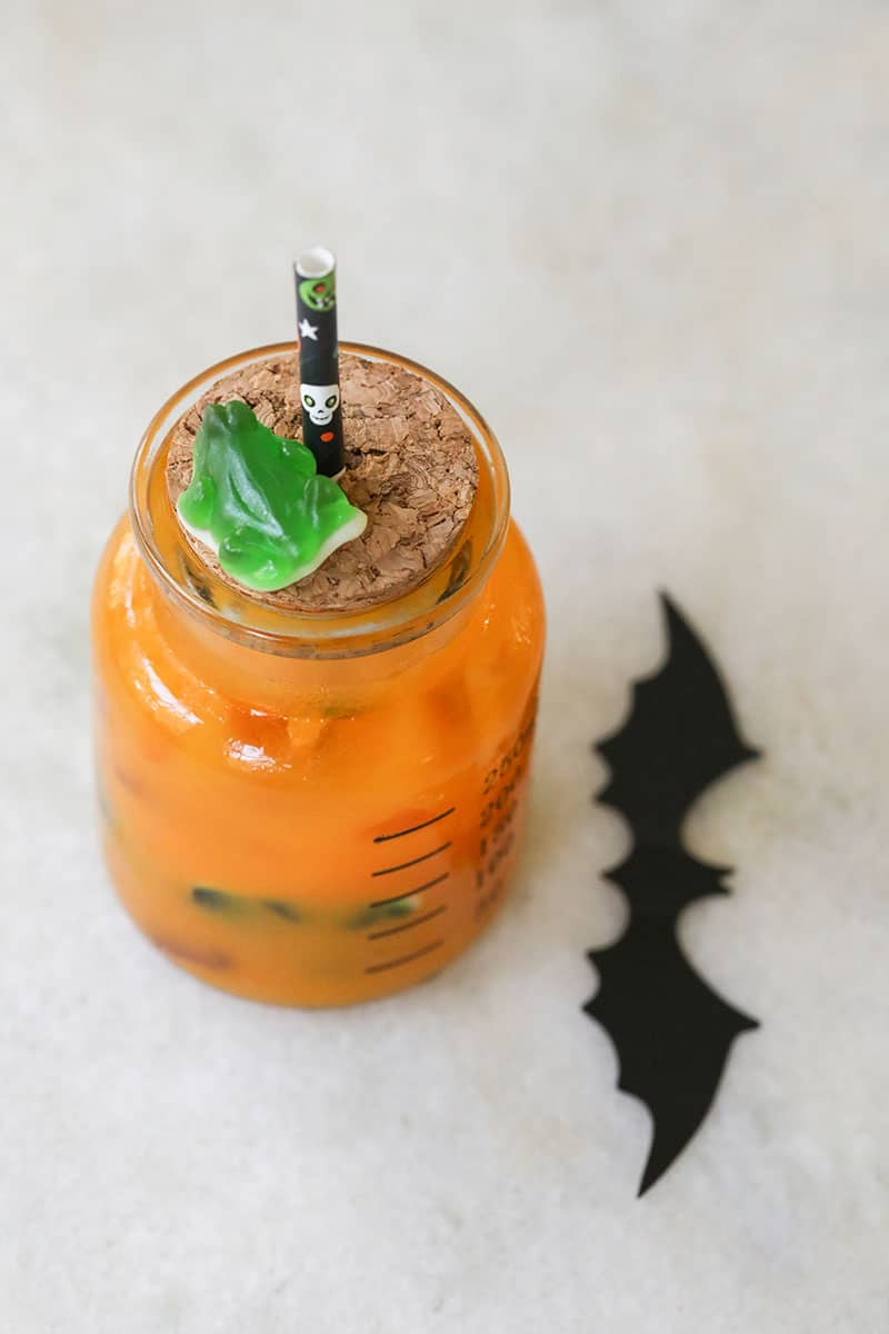 Kids Halloween punch on a marble table with a cork lid and a black Halloween straw.