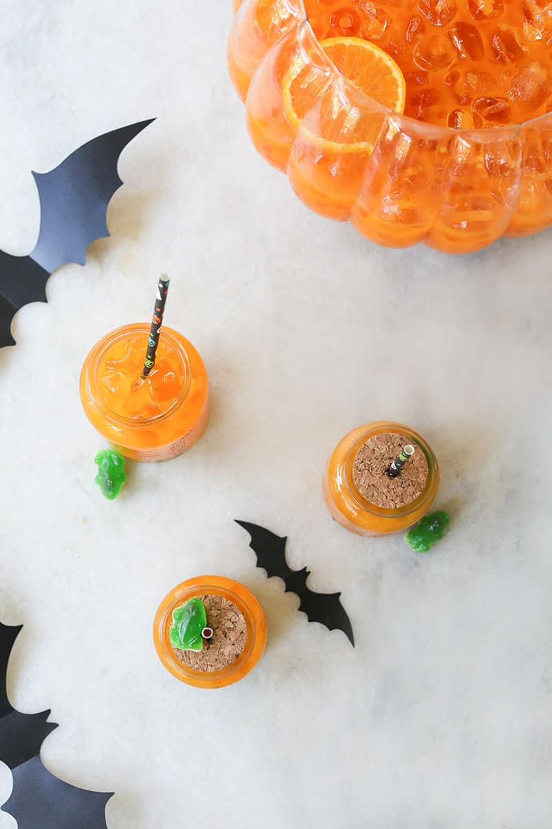 Halloween orange punch on a marble table with bats.