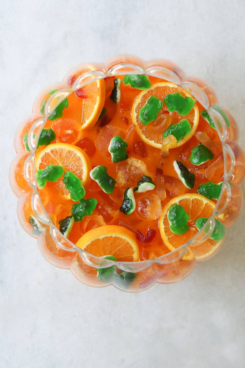 Overhead of an orange Halloween punch for kids with green frog mummies and gummy worms.