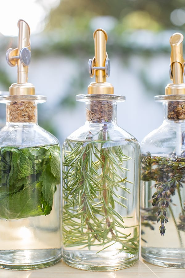 Three bottles of infused simple syrup with rosemary, mint and lavender.