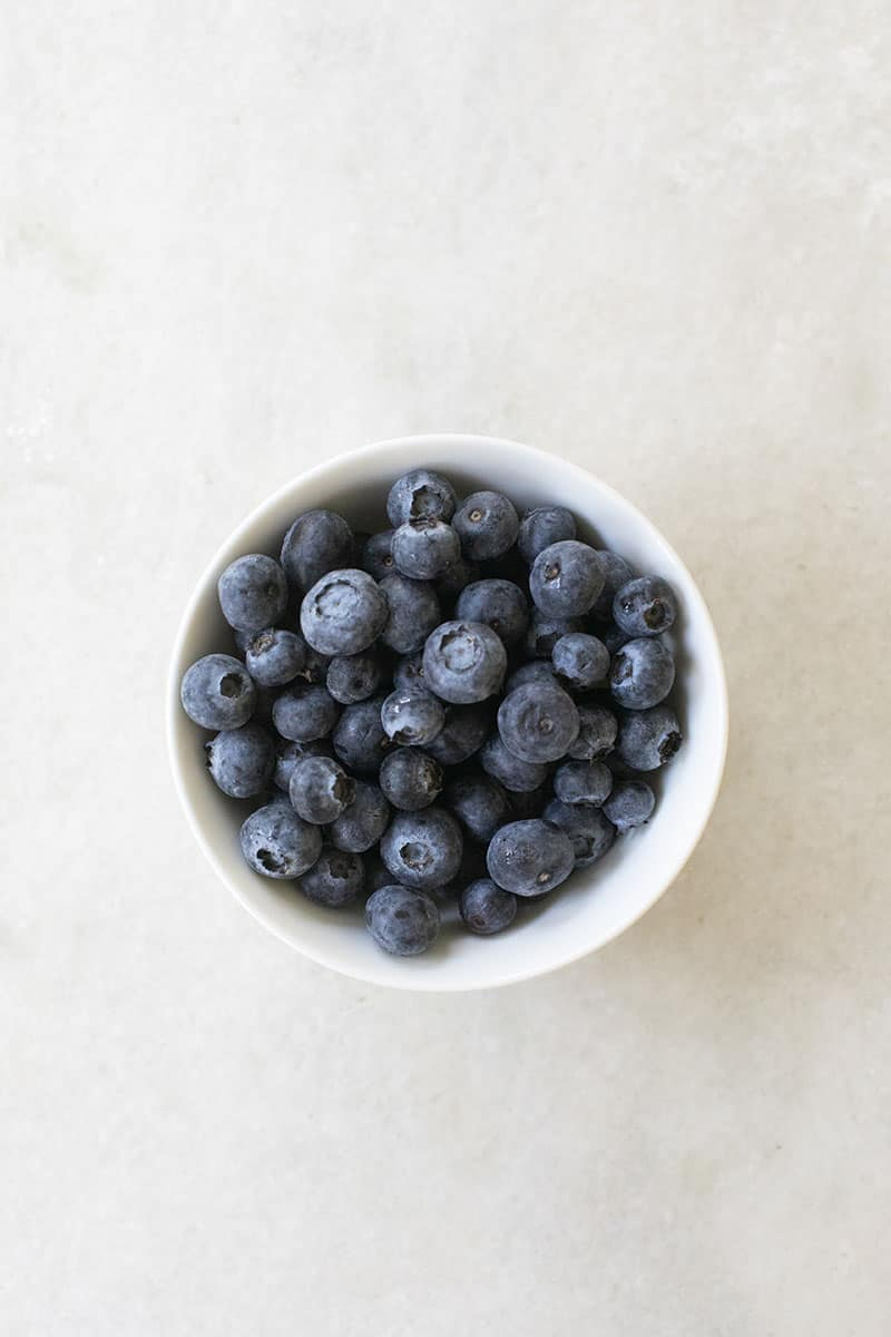 Fresh blueberries in a white bowl on a marble table.