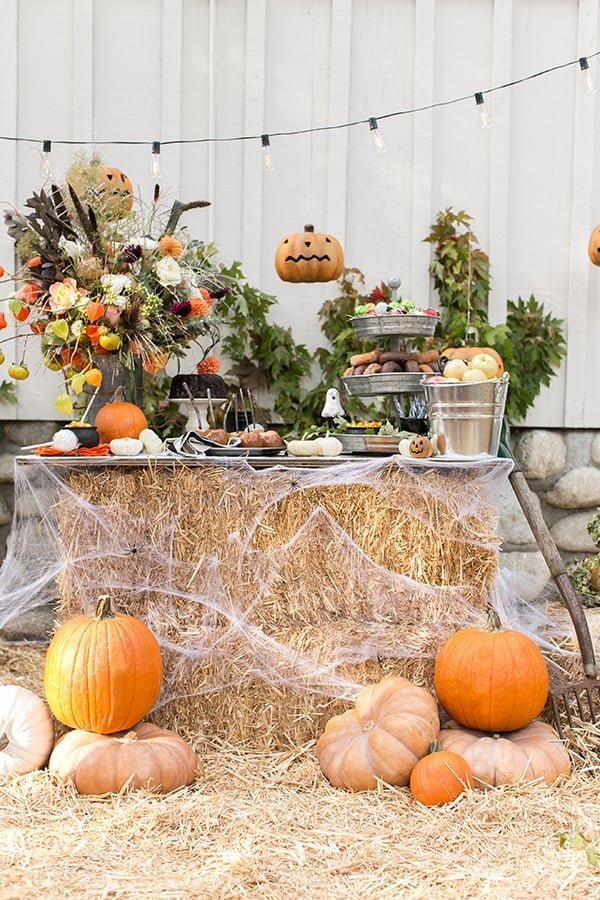 A Halloween party ideas set-up with hay stacks, tin buckets, pumpkins and string lights.