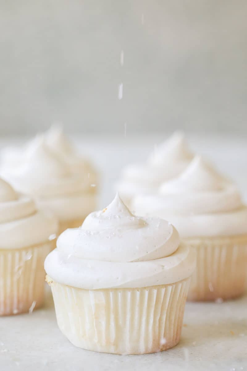vanilla cupcake recipe with buttercream frosting and sprinkles being poured over the top.