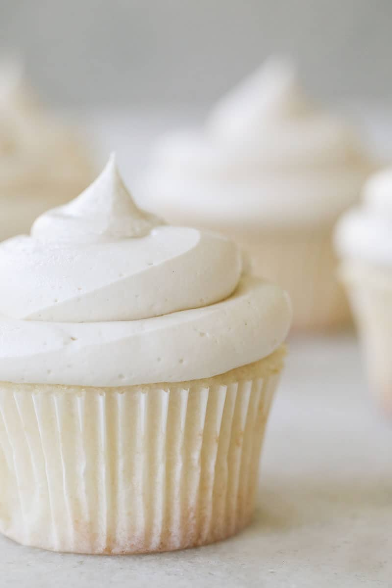 A fluffy white vanilla cupcake with a whit paper and creamy buttercream.