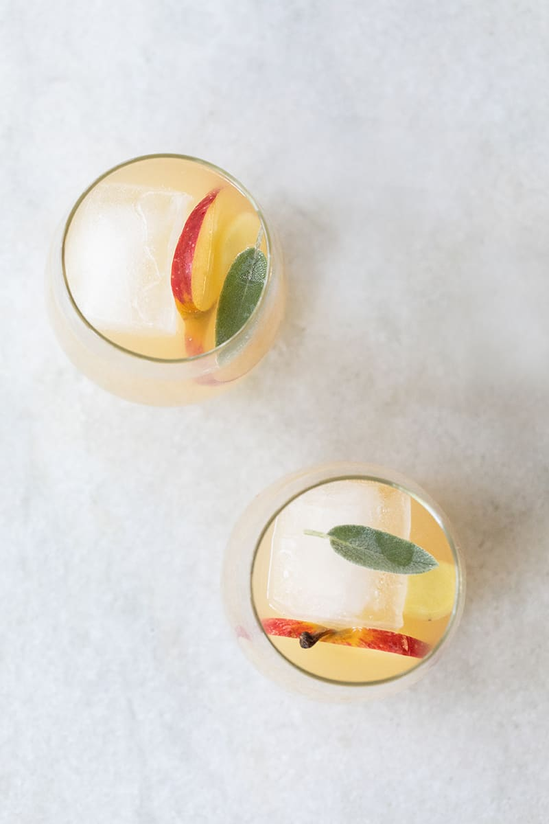 Fall wine spritzers on a marble table with apple, ginger, sage, white wine, Lillet.