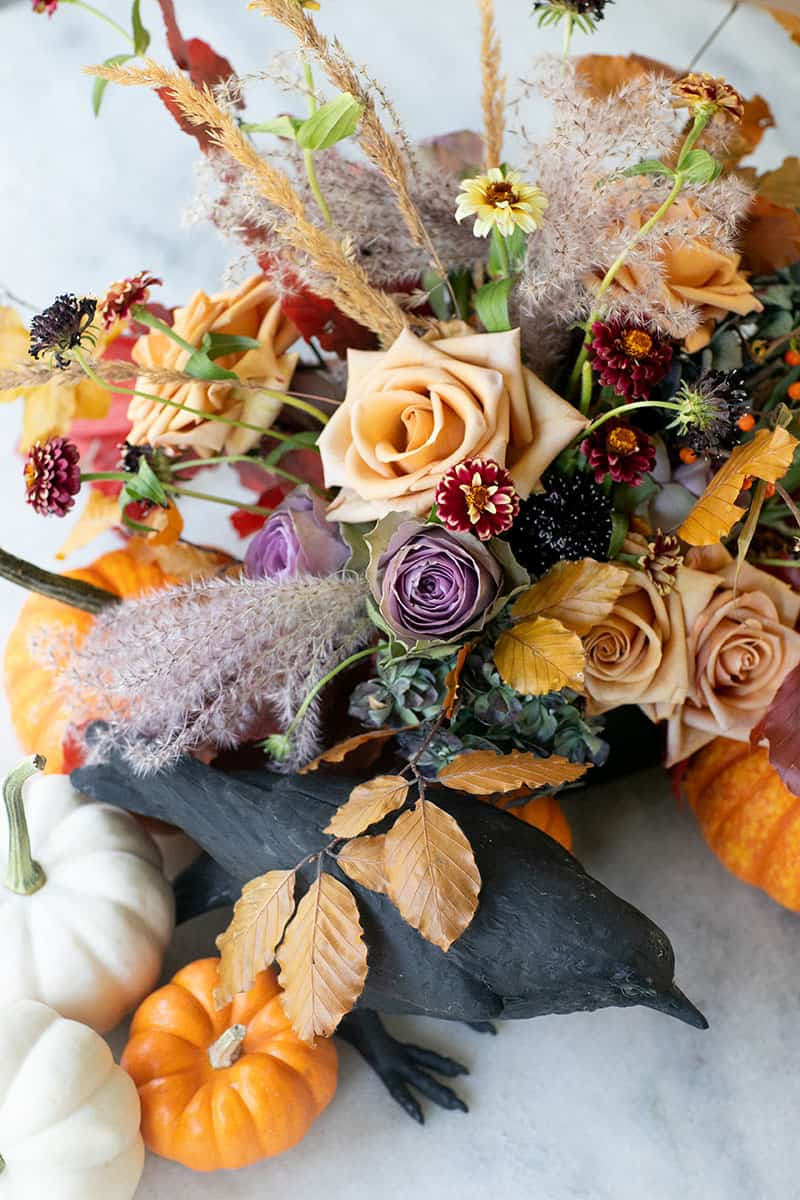 Halloween flowers and pumpkin and crow on a marble table.