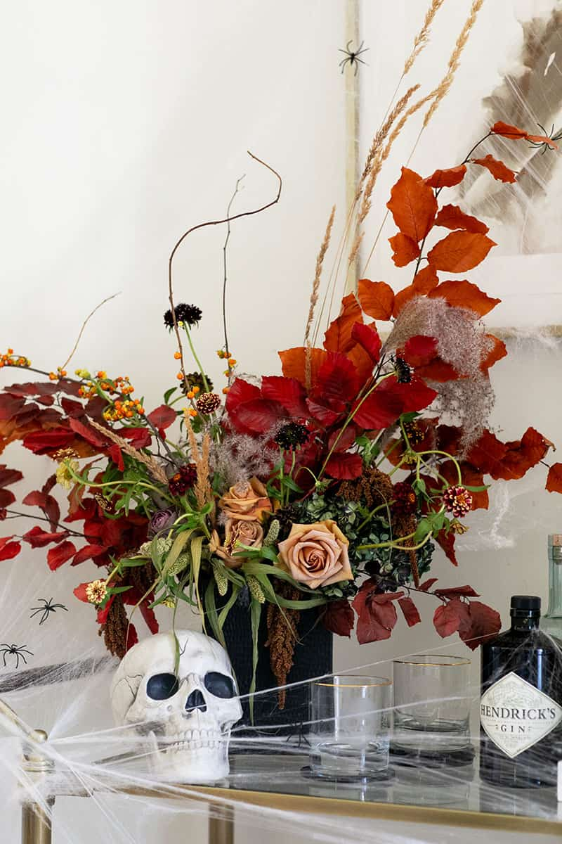 Beautiful Halloween flowers with skull and glasses on a bar cart for an inexpensive​ Halloween decorating idea.