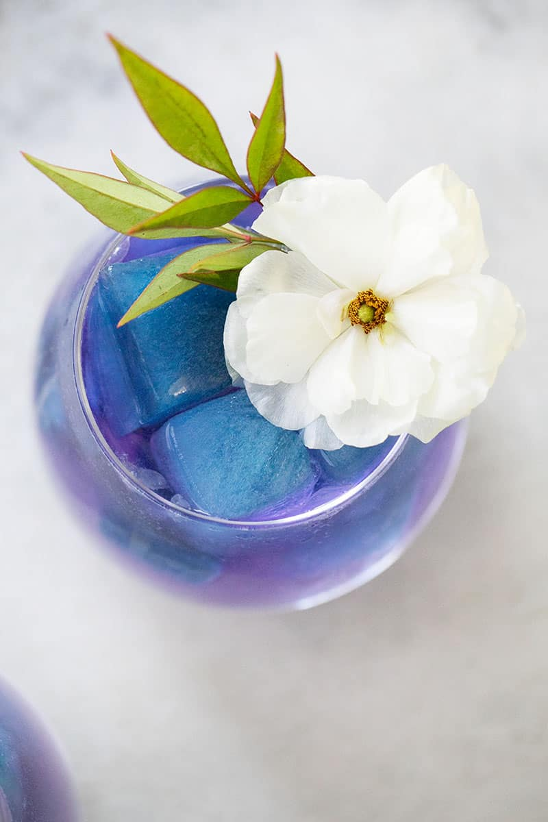 Mermaid inspired cocktail with blue ice cubes and a white flower.