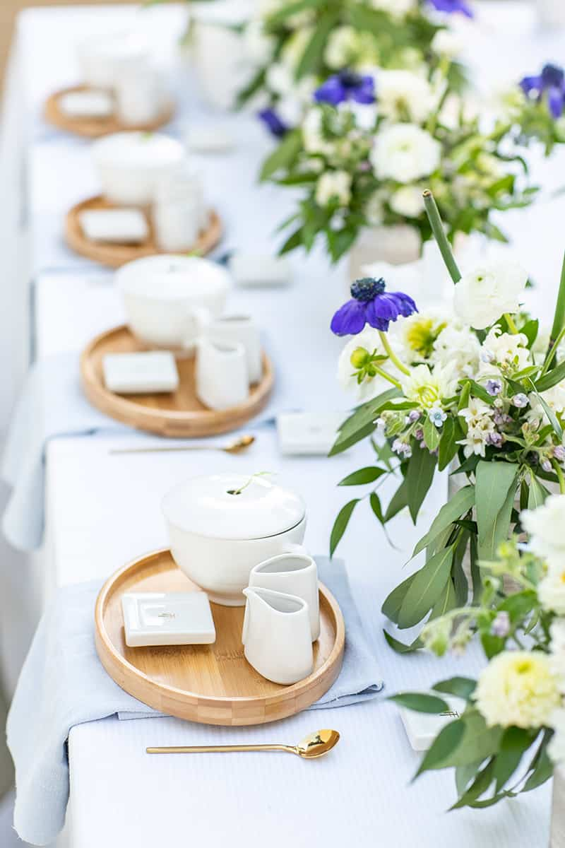 Tea party cups and flowers on a table for a bridal shower tea party.