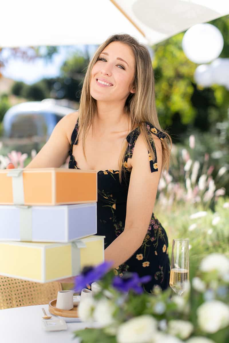Eden Passante holding three boxes of tea at a tea party bridal shower