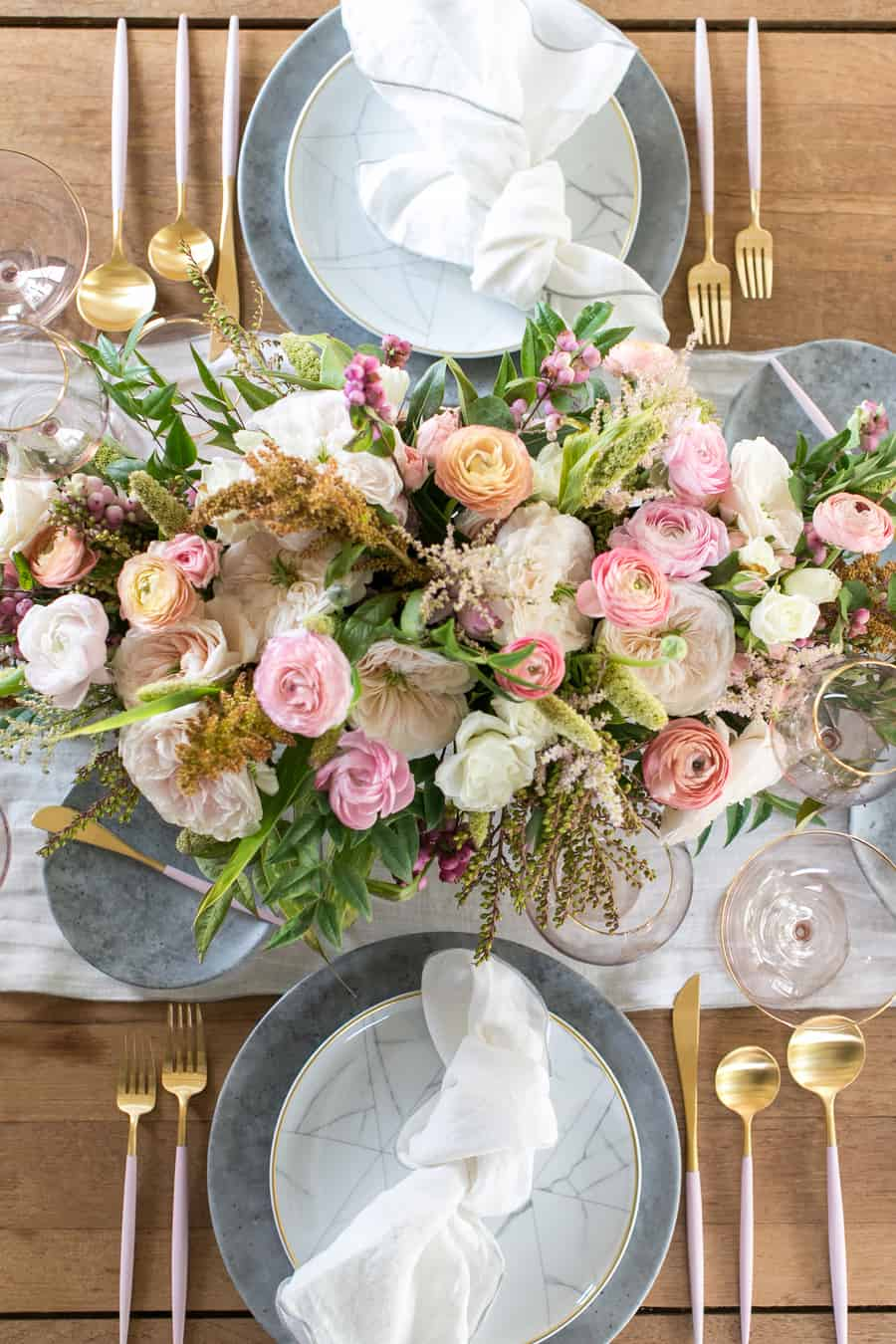 A modern table setting with flowers, plates, forks on a wooden table.