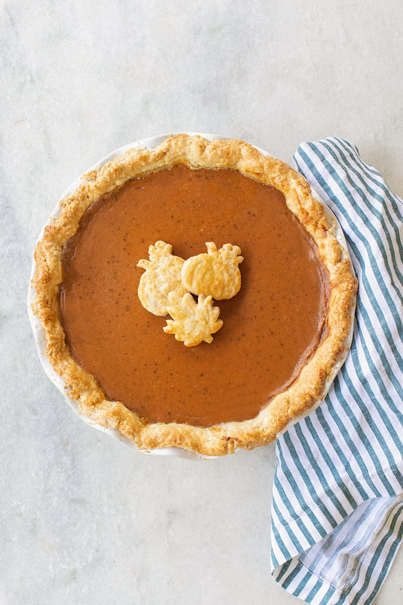 Homemade pumpkin pie on a marble table with a blue and white striped napkin.