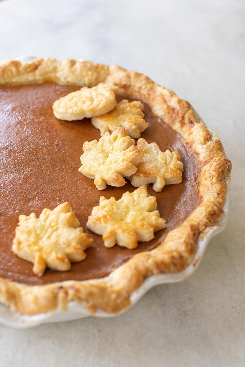 Beautiful pumpkin pie with leaf cutouts.