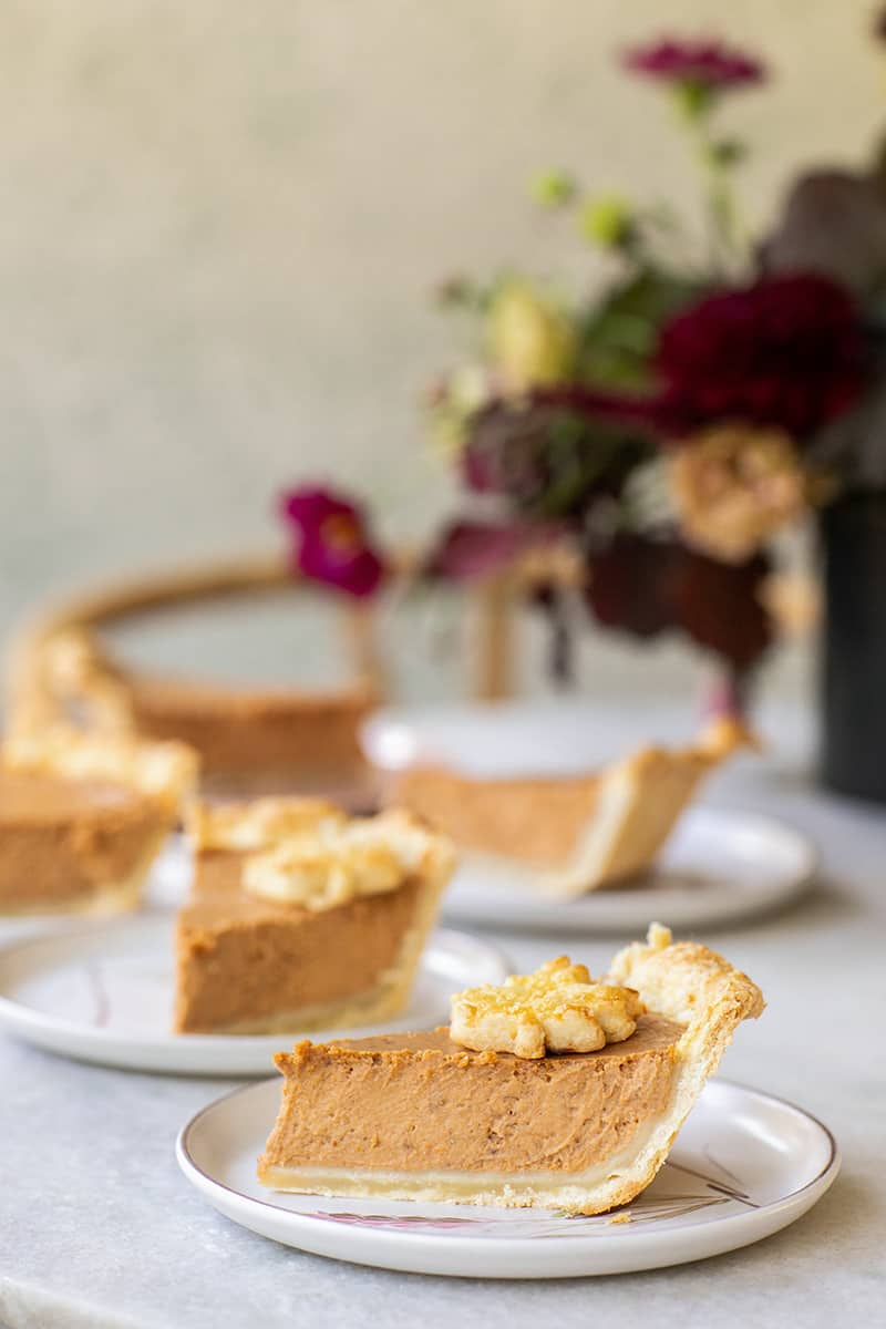 Slices of pumpkin pie on white plates.
