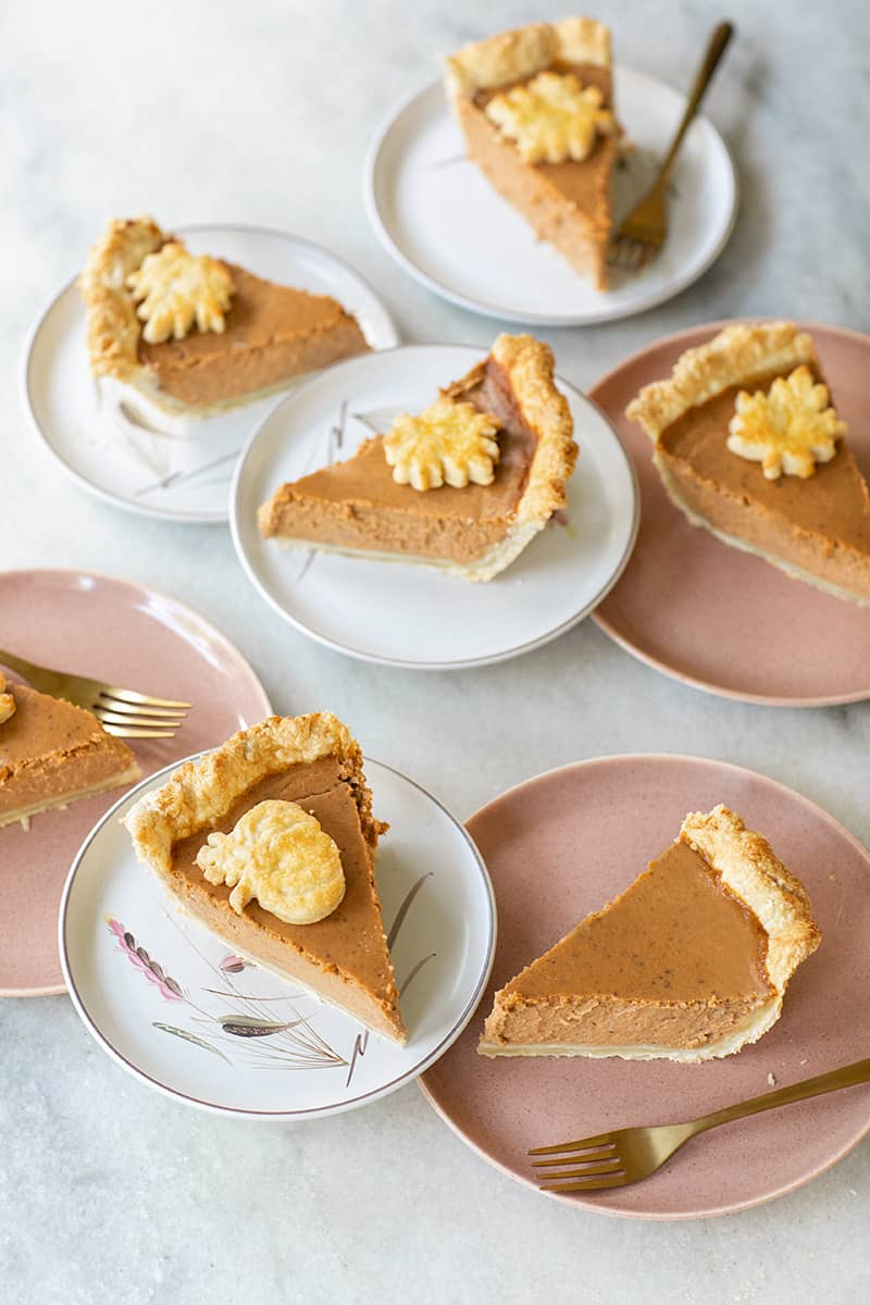 Slices of Thanksgiving pies on plates on a marble table.