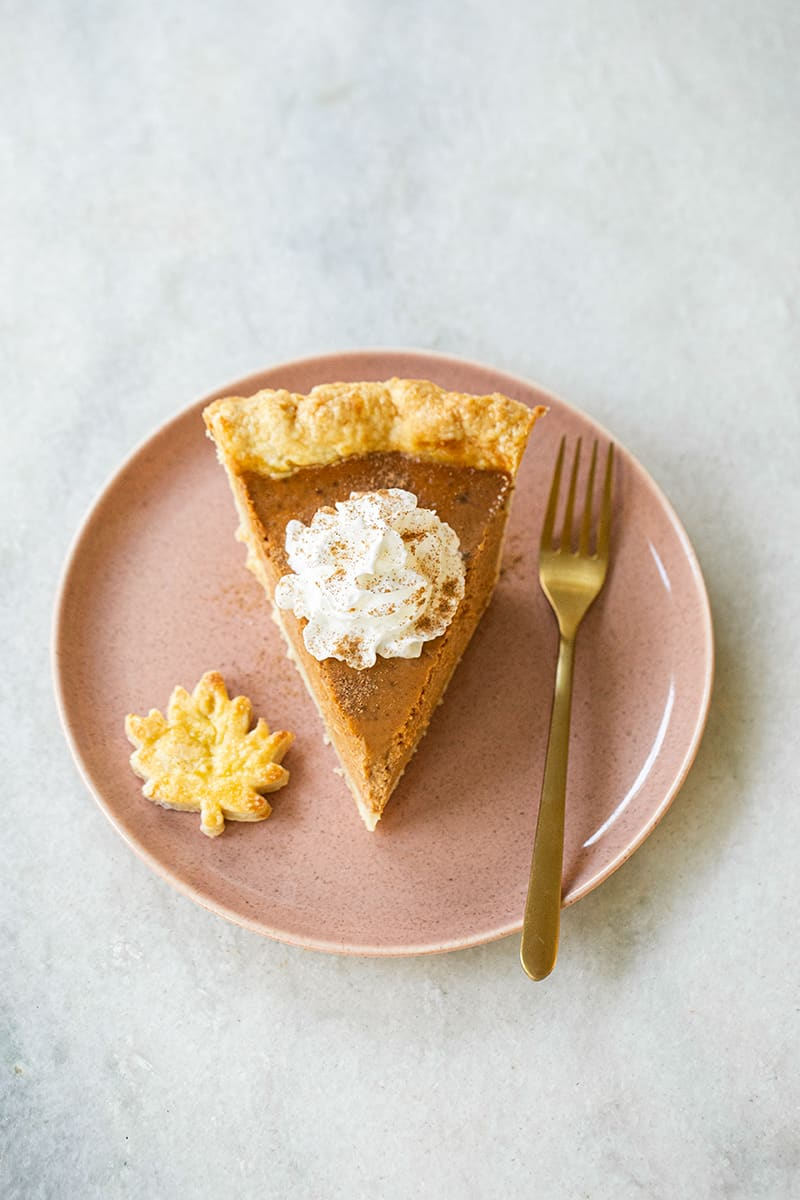 Slice of the best pumpkin pie on a pink plate with a gold spoon topped with whipped cream.